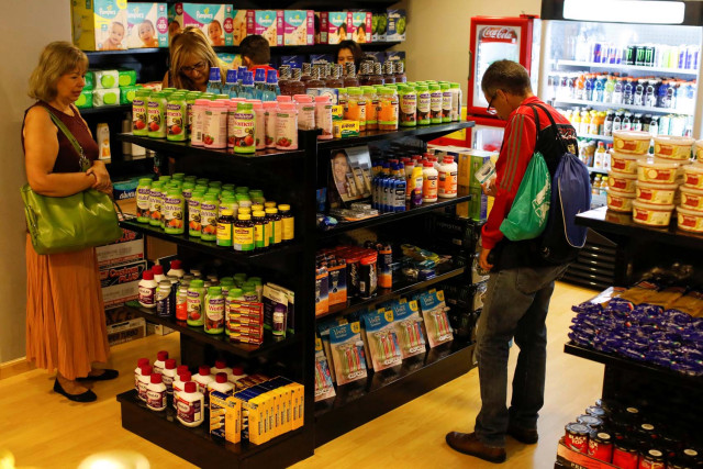 People shop inside a convenience store at a five-star hotel in Caracas, Venezuela October 12, 2018. Picture taken October 12, 2018. REUTERS/Marco Bello
