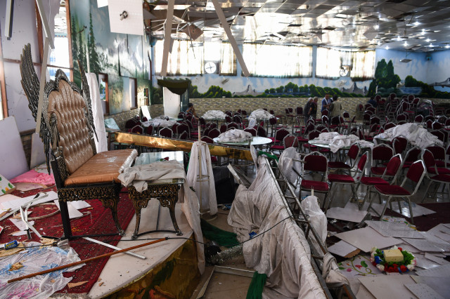 Afghan men investigate in a wedding hall after a deadly bomb blast in Kabul on August 18, 2019. - More than 60 people were killed and scores wounded in an explosion targeting a wedding in the Afghan capital, authorities said on August 18, the deadliest attack in Kabul in recent months. (Photo by Wakil KOHSAR / AFP)