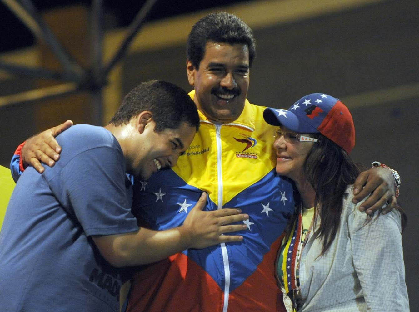 "(FILES) This file picture taken on April 6, 2013 shows Venezuelan acting President Nicolas Maduro (C) embracing his wife Cilia Flores (L) and son Nicolas Maduro during a campaign rally in Puerto Ordaz, Bolivar state, Venezuela. Nicolas Ernesto Maduro Guerra, ""Nicolasito"", the President's son is an economist and candidate to July 31, 2017 ""constituent assembly"". / AFP PHOTO / JUAN BARRETO"