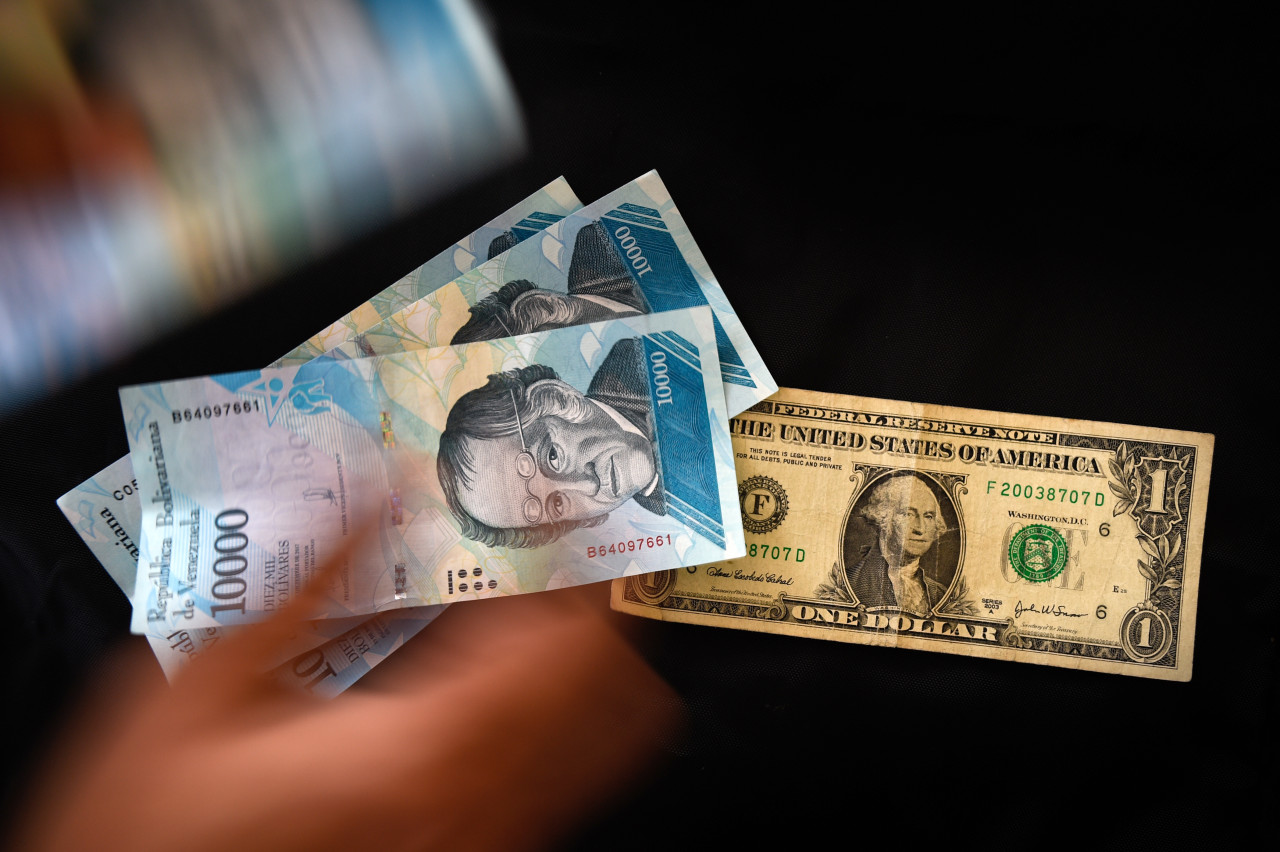 A man counts Venezuelan bolivar banknotes next to a US one-dollar bill in Caracas on August 2, 2018. Venezuela's government on Thursday loosened the tight currency controls it first put in place 15 years ago, with the pro-government Constituent Assembly announcing the passage of a decree authorizing money exchange operations. / AFP PHOTO / Federico PARRA
