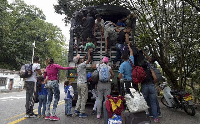 "Venezuelan migrants climb on a truck on the road from Cucuta to Pamplona, in Norte de Santander Department, Colombia, on February 10, 2019. - Opposition leader Juan Guaido, recognized by some 50 countries as Venezuela's interim president, warned the military Sunday that blocking humanitarian aid from entering the country is a ""crime against humanity."" (Photo by Raul ARBOLEDA / AFP)"