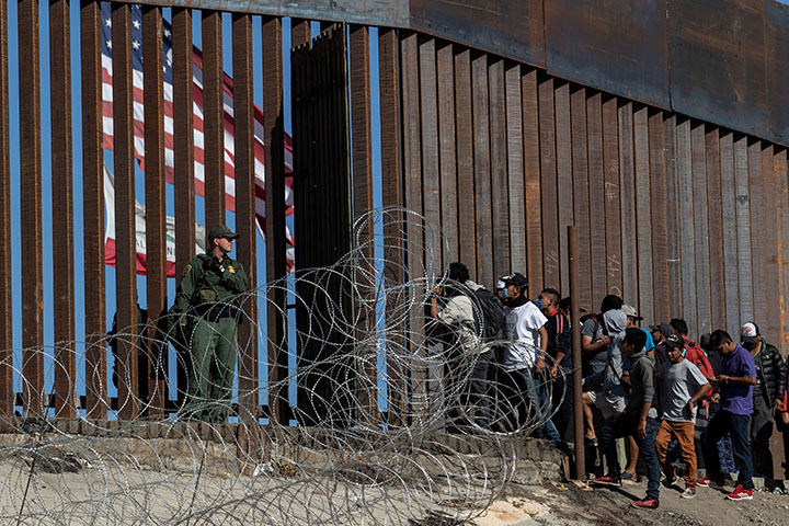 "(FILES) In this file photo taken on November 25, 2018 Central American migrants look through a border fence as a US Border PatRol agents stands guard near the El Chaparral border crossing in Tijuana, Baja California State, Mexico. - Agence France-Press (AFP) photographer Guillermo Arias on September 7, 2019 won the top prize at photojournalism's biggest annual festival for his coverage of migrants from Central America. Arias, who is from Mexico, scooped the Visa d'Or for News, the most prestigious award handed out at the ""Visa Pour L'Image"" festival in Perpignan, southwestern France. (Photo by GUILLERMO ARIAS / AFP)"