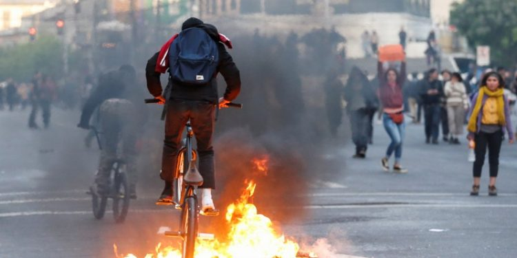 A demonstrator cycles over burning objects on a road during a protest against the government in Valparaiso, Chile October 19, 2019. REUTERS/Rodrigo Garrido Referencial