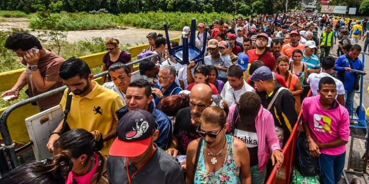 Venezuelan citizens enter Cucuta, Norte de Santander Department, Colombia from San Antonio del Tachira, Venezuela at the Simon Bolivar international bridge on July 25, 2017. Some 25.000 Venezuelans cross to Colombia and return to their country daily with food, consumables and money from ilegal work, according to official sources. Also, there are 47.000 Venezuelans in Colombia with legal migratory status and another 150.000 who have already completed the 90 allowed days and are now without visa.  / AFP PHOTO / Luis Acosta