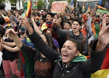 Supporters of Bolivia's main opposition presidential candidate, former president (2003-2005) Carlos Mesa, shout slogans against supporters of president and candidate Evo Morales, as both groups gather outside the hotel where the Supreme Electoral Tribunal has its headquarters to count the election votes, in La Paz, on October 21, 2019. - Evo Morales, seeking a controversial fourth term, led Bolivia's presidential election race Sunday but faces a historic second round run-off against Mesa, partial results showed. Morales had 45 percent of the vote to Mesa's 38 percent, the Supreme Electoral Tribunal announced, with most of the votes counted. (Photo by Aizar RALDES / AFP)