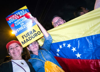 "A Venezuelan resident in Costa Rica holds a sign reading ""our voices are here, our hearts are in Venezuela, Maduro out"" as people gather outside the house of former Costa Rican president and Nobel Peace Prize winner Oscar Arias in San Jose, Costa Rica, January 23, 2019, to thank him for his position against the government of Nicolas Maduro. - The United States and major South American nations recognised Venezuelan opposition leader Juan Guaido as interim leader on January 23 while the EU called for free elections to restore democracy, leaving President Nicolas Maduro increasingly isolated. (Photo by Ezequiel BECERRA / AFP)"