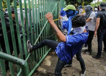 An anti-government protester kicks a riot police shield during a protest of students and relatives of political prisoners in front of a police line at the Universidad Centroamericana (UCA) in Managua on November 19, 2019. - Last week about 16 people were arrested and prosecuted for bringing water to mothers of political prisoners who were going on a hunger strike in Masaya. (Photo by INTI OCON / AFP)