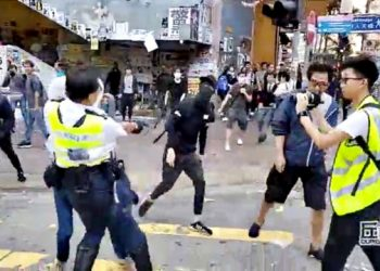 A still image from a social media video shows a police officer aiming his gun as a protester in Sai Wan Ho, Hong Kong, China November 11, 2019.   CUPID PRODUCER via REUTERS  ATTENTION EDITORS - THIS IMAGE HAS BEEN SUPPLIED BY A THIRD PARTY. MANDATORY CREDIT. NO RESALES. NO ARCHIVES.