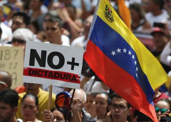 "Anti-government protesters rally to demand the resignation of Venezuelan President Nicolas Maduro, as one holds a sign that reads in Spanish ""No more dictatorship"" in Caracas, Venezuela, Monday, March 4, 2019. The United States and about 50 other countries recognize opposition Congress President Juan Guaido as the rightful president of Venezuela, while Maduro says he is the target of a U.S.-backed coup plot. (AP Photo/Eduardo Verdugo)"