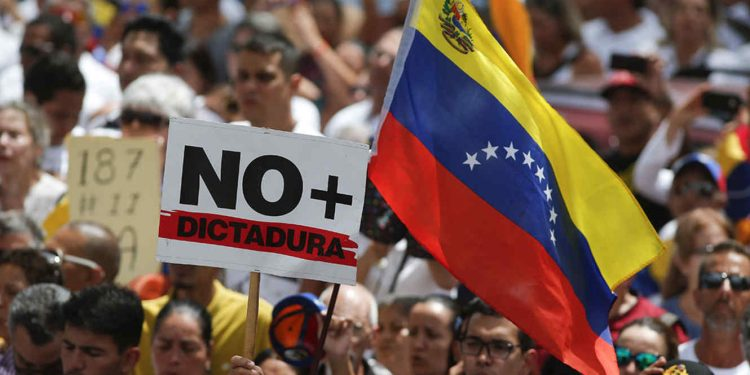 """Anti-government protesters rally to demand the resignation of Venezuelan President Nicolas Maduro, as one holds a sign that reads in Spanish """"No more dictatorship"""" in Caracas, Venezuela, Monday, March 4, 2019. The United States and about 50 other countries recognize opposition Congress President Juan Guaido as the rightful president of Venezuela, while Maduro says he is the target of a U.S.-backed coup plot. (AP Photo/Eduardo Verdugo)"""