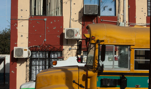 A shot school bus remains outside the Municipal Presidency in Villa Union, Coahuila state, Mexico, on December 2, 2019. - Mexican security forces were on Monday searching for the gunmen wich perpetrate the armed attack on the authorities of Villa Union over the weekend with a toll of 22 dead, including 16 of the alleged criminals. (Photo by Julio Cesar AGUILAR / AFP)