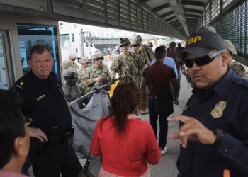 HIDALGO, TX - NOVEMBER 02: U.S. Customs and Border Protection officers and U.S. Army troops allow people to pass over the international bridge with Mexico to an immigration checkpoint on November 2, 2018 in Hidalgo, Texas. U.S. President Donald Trump ordered the troops to the border to bolster security at points where an immigrant caravan may attempt to cross in upcoming weeks.   John Moore/Getty Images/AFP
