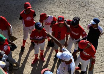 Youngsters listen to instructions from their coach during a training session at the Criollitos de Venezuela baseball school in Caracas, on October 31, 2019. - For over six decades, the Criollitos de Venezuela school has been the seedbed for big names of the baseball major leagues such as Andres Galarraga, Omar Vizquel or Jose Altuve. But currently the school fights for its survival since fewer and fewer children can follow the steps of old myths due to the country's economic crisis. (Photo by Yuri CORTEZ / AFP)