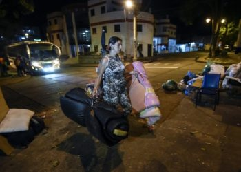 (FILES) In this file picture taken on December 18, 2019 A Venezuelan migrant carries mattresses to rest at a park in Bucaramanga, Colombia. - Dozens of Venezuelan migrants have turned the Colombian city of Bucaramanga into a large open-air bedroom. Several of the city's 244 parks are transformed into improvised camps at night. (Photo by Juan BARRETO / AFP)