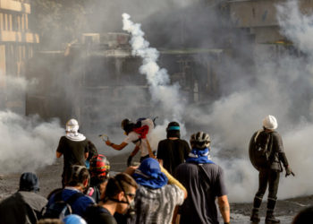 Demonstrators clash with riot police during a protest against the government of President Sebastian Pinera, in Santiago, on January 24, 2020. - Demonstrations which began on October 18, 2019, initially against a modest metro fare hike, quickly escalated and left 29 people dead amid accusations of a heavy-handed response from security forces. (Photo by Martin BERNETTI / AFP)