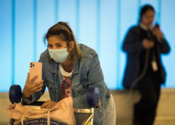 Passengers wear protective masks to protect against the spread of the Coronavirus as they arrive at the Los Angeles International Airport, California, on January 22, 2020. - A new virus that has killed nine people, infected hundreds and has already reached the US could mutate and spread, China warned on January 22, as authorities urged people to steer clear of Wuhan, the city at the heart of the outbreak. (Photo by Mark RALSTON / AFP)