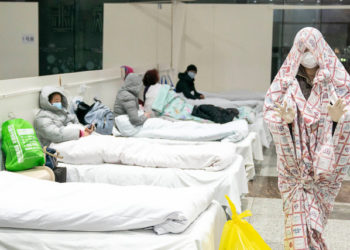 This photo taken on February 5, 2020 shows a patient (R) covered with a bed sheet at an exhibition centre converted into a hospital as it starts to accept patients displaying mild symptoms of the novel coronavirus in Wuhan in China's central Hubei province. - China scrambled to find bed space for thousands of newly infected patients on February 6, as the toll from a deadly new virus jumped again with more than 28,000 people known infected nationwide and 563 deaths. (Photo by STR / AFP) / China OUT