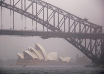 FILE PHOTO: A boat passes under the Sydney Harbour Bridge and in front of the Sydney Opera House as strong winds and heavy rain hit the city of Sydney, Australia, November 28, 2018.    REUTERS/David Gray