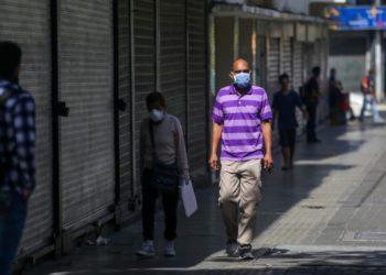 """People wear face masks as a precautionary measure against the spread of the new coronavirus, COVID-19, in Caracas, on March 16, 2020. - Venezuelan President Nicolas Maduro ordered on Sunday a """"collective quarantine"""" in seven states, including the capital Caracas, from Monday to stem the spread of the new coronavirus pandemic. (Photo by Cristian Hernandez / AFP)"""