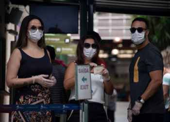 Tourists wears face masks after buying tickets at the Corcovado hill train station, to go up to see the statue of Christ the Redeemer in Rio de Janeiro, Brazil, on March 17, 2020. - Rio de Janeiro's state government closed the iconic Christ the Redeemer statue and the cable car to Sugarloaf Mountain, two of the city's most famous attractions, as an emergency measure to stop the spread of the new coronavirus COVID-19. (Photo by MAURO PIMENTEL / AFP)