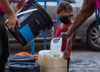 A child wears a face mask as a preventive measure against the global COVID-19 coronavirus pandemic as his caretaker collects water in Caracas, on March 27, 2020. - Venezuela is facing the novel coronavirus pandemic while suffering a major gasoline shortage and with the country's water system collapsed, which has left many homes without running water. (Photo by Cristian Hernandez / AFP)