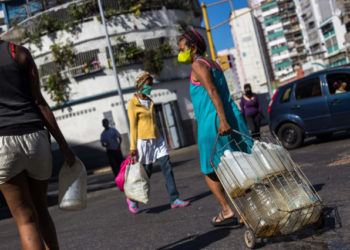 People wear face masks as a preventive measure against the global COVID-19 coronavirus pandemic as they carry water cans collected from a street pipe in Caracas, on March 27, 2020. - Venezuela is facing the novel coronavirus pandemic while suffering a major gasoline shortage and with the country's water system collapsed, which has left many homes without running water. (Photo by Cristian Hernandez / AFP)