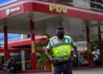 A member of Baruta Municipal Police stands guard near a gas station wearing a face mask as a precautionary measure against the spread of the new coronavirus, COVID-19, in Caracas on March 23, 2020. - Venezuela is facing the novel coronavirus pandemic while suffering a major gasoline shortage and with the country's water system collapsed, which has left many homes without running water. (Photo by Cristian Hernandez / AFP)