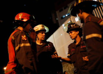 """Firefighters talk in the surrounding area of the skyscraper known as the """"Tower of David"""" after an earthquake in Caracas, Venezuela August 21, 2018. REUTERS/Carlos Garcia Rawlins"""