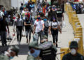 People walk out of a public market wearing protective masks during the national quarantine in response to the spread of coronavirus disease (COVID-19) in Caracas, Venezuela, March 21, 2020. REUTERS/Manaure Quintero