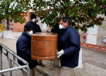 Employees of a mortuary carry the coffin of a person who died from the coronavirus disease (COVID-19), during the partial lockdown to combat the disease outbreak, at the Carabanchel cemetery in Madrid, Spain, March 27, 2020. REUTERS/Juan Medina