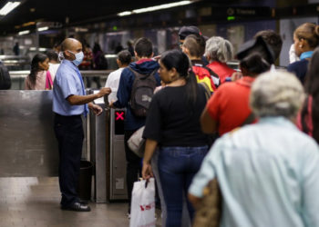 A subway worker wearing a face mask (L) receive tickets at the subway station in the face of the global COVID-19 coronavirus pandemic, in Caracas, on March 13, 2020. (Photo by CRISTIAN HERNANDEZ / AFP)