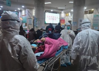 In this photo taken on January 25, 2020, medical staff wearing protective clothing to protect against a previously unknown coronavirus arrive with a patient at the Wuhan Red Cross Hospital in Wuhan. - The number of confirmed deaths from a viral outbreak in China has risen to 54, with authorities in hard-hit Hubei province on January 26 reporting 13 more fatalities and 323 new cases. (Photo by Hector RETAMAL / AFP)