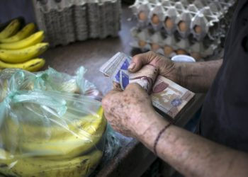 A clerk counts Venezuelan bolivar banknotes after selling goods to a customer at a fruit and vegetable store in Caracas July 10, 2015. A debilitating recession and a drop in oil prices have harmed the OPEC nation's ability to provide dollars through its complex three-tiered currency control system, pushing up the black market rate at a dizzying speed. The bolivar sank past 600 per U.S. dollar on Thursday, compared with 73 a year ago, according to anti-government website DolarToday. REUTERS/Marco Bello