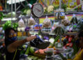 A woman wearing a face mask as a preventive measure against the spread of the new coronavirus, COVID-19, buys groceries at a municipal market in Caracas, on March 20, 2020. (Photo by Federico PARRA / AFP)