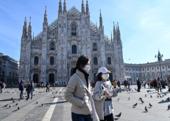Two women wearing a protective facemask walk across the Piazza del Duomo, in front of the Duomo, in central Milan, on February 24, 2020 closed following security measures taken in northern Italy against the COVID-19 the novel coronavirus. - Italy reported on February 24, 2020 its fourth death from the new coronavirus, an 84-year old man in the northern Lombardy region, as the number of people contracting the virus continued to mount. (Photo by ANDREAS SOLARO / AFP)