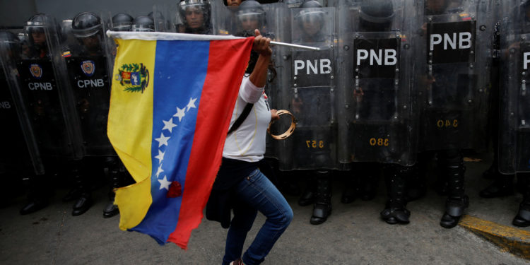 A woman waves a Venezuelan flag in front of security forces during a demonstration in Caracas, Venezuela March 10, 2020. REUTERS/Manaure Quintero