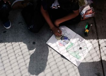 BROWNSVILLE, TX - JUNE 25:  A Honduran child works in a coloring book while waiting with his family along the border bridge after being denied entry from Mexico into the U.S. on June 25, 2018 in Brownsville, Texas. Immigration has once again been put in the spotlight as Democrats and Republicans spar over the detention of children and families seeking asylum at the border. Before President Donald Trump signed an executive order last week that halts the practice of separating families who are seeking asylum, more than 2,300 immigrant children had been separated from their parents in the zero-tolerance policy for border crossers.  (Photo by Spencer Platt/Getty Images)