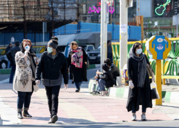 Iranian pedestrians walk while wearing protective masks in Tehran on March 10, 2020 amid the spread of coronavirus in the country. - Iran today reported 54 new deaths from the novel coronavirus in the past 24 hours, the highest single-day toll since the start of the country's outbreak. (Photo by ATTA KENARE / AFP)