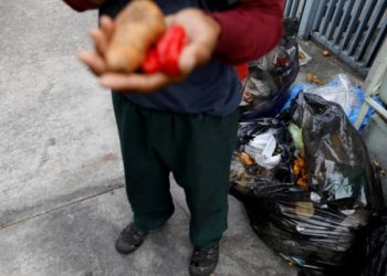 A man holds vegetables after he scavenges for food in a rubbish bin in Caracas, Venezuela February 27, 2019. Picture taken February 27, 2019. REUTERS/Carlos Jasso