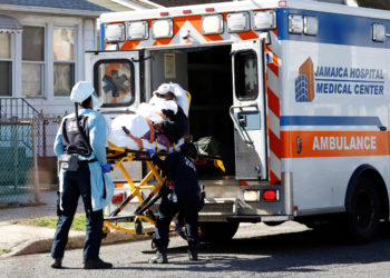 FILE PHOTO: Emergency Medical Technicians (EMT) lift a patient into an ambulance while wearing protective gear, as the outbreak of coronavirus disease (COVID-19) continues, in New York City, New York, U.S., March 24, 2020. REUTERS/Stefan Jeremiah/File Photo