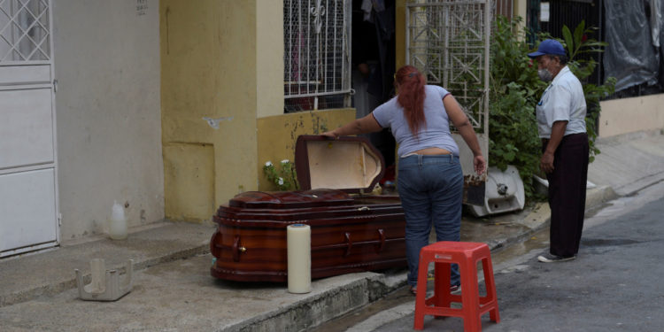 A woman looks into a coffin holding the dead body of her mother after she died at home yesterday, during the outbreak of the coronavirus disease (COVID-19), in Guayaquil, Ecuador March 31, 2020. REUTERS/Vicente Gaibor del Pino NO RESALES. NO ARCHIVES