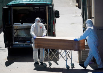 Mortuary workers push a coffin of a person who died at a nursing home during the coronavirus disease (COVID-19) outbreak in Leganes Madrid, near Madrid, Spain, April 2, 2020. REUTERS/Juan Medina