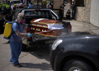 """A worker sprays disinfectant on a vehicle carrying a coffin lined up to enter a cemetery as Ecuador's government announced on Thursday it was building a """"special camp"""" in Guayaquil for coronavirus disease (COVID-19) victims, in Guayaquil, Ecuador April 2, 2020. REUTERS/Vicente Gaibor del Pino NO RESALES. NO ARCHIVES"""