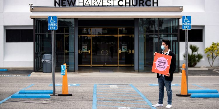 A volunteer welcomes the cars of the parishioners with a poster reading 'Flash Your Lights If You're Grateful' during a drive-in Easter mass at the New Harvest Church amid the coronavirus pandemic in Norwalk, south of Los Angeles, California, USA. EFE/ETIENNE LAURENT