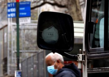A bus driver and a pedestrian both wear protective face masks in Harlem, New York, USA, 10 April 2020. EFE/EPA/PETER FOLEY
