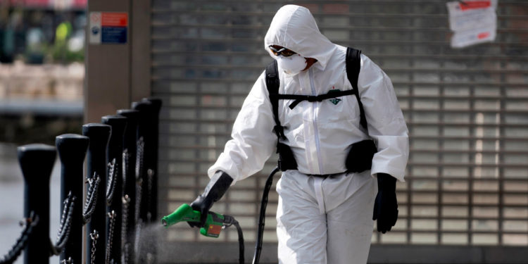 London (United Kingdom), 31/03/2020.- A cleaner sprays disinfectant outside the Emirates Air Line office in Central London, Britain, 31 March 2020. According to news reports, the NHS is anticipating a Coronavirus 'tsunami' as the peak of infection rates nears. British Prime Minister Boris Johnson has announced that Britons can only leave their homes for essential reasons or may be fined, in order to reduce the spread of the Coronavirus. (Reino Unido, Londres) EFE/EPA/WILL OLIVER