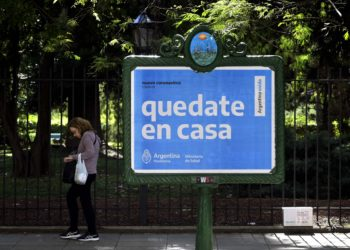 "A woman walks near a board advertising Health Ministry advise reading ""Stay at home"" during the outbreak of the new Coronavirus, COVID-19, in Buenos Aires, Argentina on March 19, 2020. (Photo by JUAN MABROMATA / AFP)"