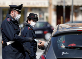 Carabinieri wearing protective face masks verify if a driver has a valid reason to travel during the lockdown to prevent the spread of coronavirus disease (COVID-19), at Piazza Venezia in Rome, Italy, March 21, 2020. REUTERS/Yara Nardi