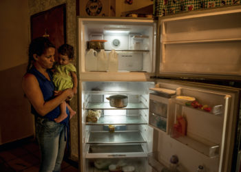 Wuendy Perez, a single mother with five children, with her youngest daughter, Wuendy Joselin, 1, next to their nearly empty refrigerator, in La Guaira, Venezuela, June 16, 2017. The economic collapse has taken a large toll on the economy and people here, leaving residents struggling to make ends meet amid widespread shortages and soaring food prices. (Meridith Kohut/The New York Times)   CONTACTO