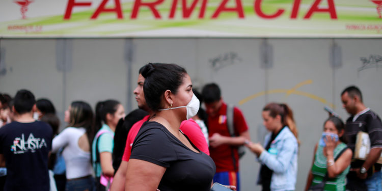 A woman wears a protective mask while people queue outside the pharmacy in response to coronavirus (COVID-19) spread, in Caracas, Venezuela March 13, 2020. REUTERS/Carlos Jasso